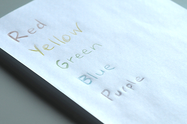 A sheet of paper with the primary colors written down with crayons