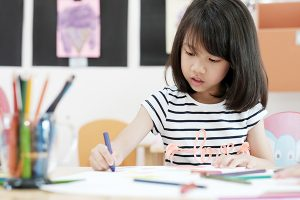 A young kid sits at a desk coloring with crayons
