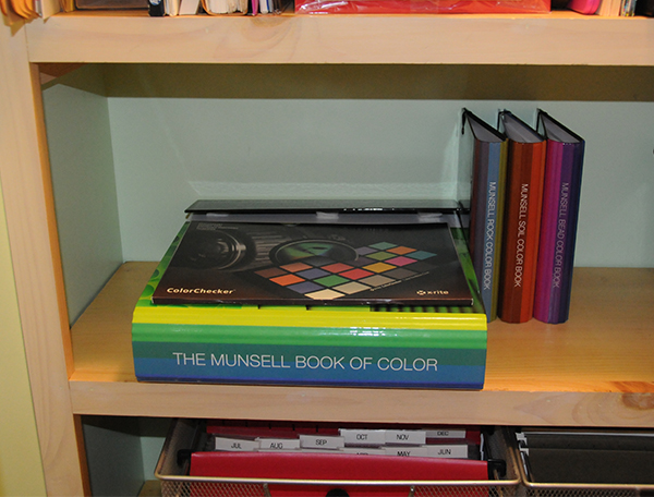 A stack of Munsell color books and charts in a closet being properly stored