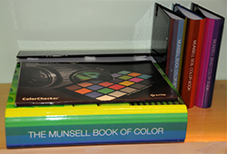 A stack of Munsell color books and charts in storage