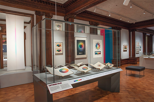 Color books on display in a case with color charts and graphs on the wall in the background at Cooper Hewitt Museum