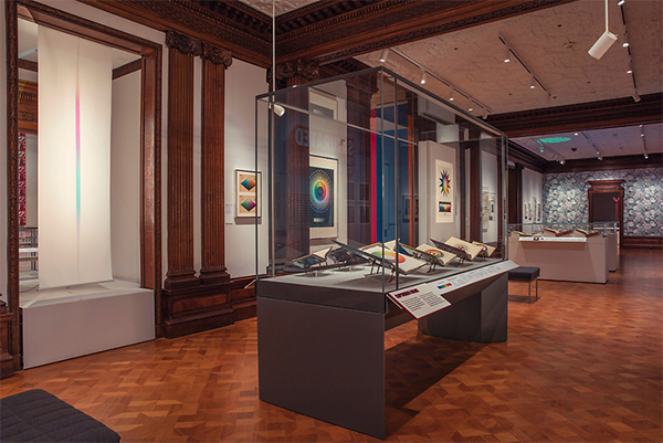 The Saturated exhibit at Cooper Hewitt showing color optic tools, books and charts in displays and on the gallery walls