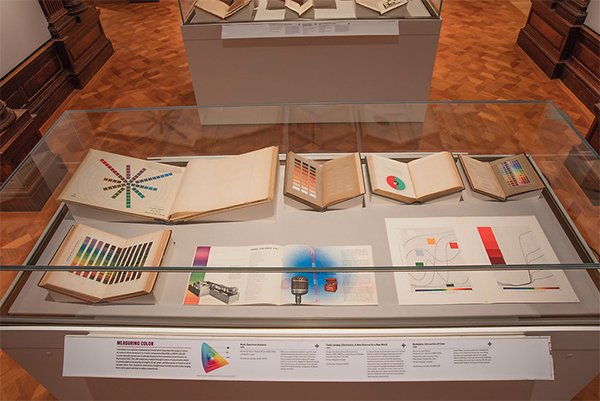 Color books on display in a case at the Cooper Hewitt Saturated exhibition