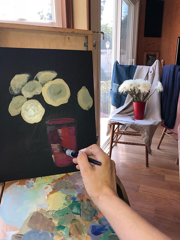 Masha Hemmerling working on a painting of a bouquet of chrysanthemums in its very early stages