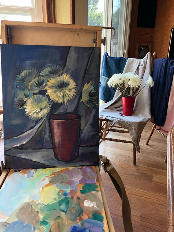Masha Hemmerling working on a painting of a bouquet of chrysanthemums in mid stage