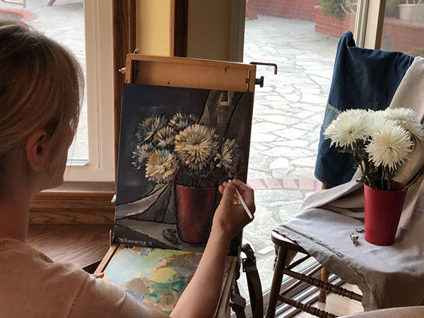 Masha Hemmerling working on a painting of a bouquet of chrysanthemums nearing its completion