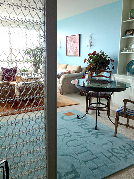 An aqua rug that says words like speak, truth, wish on the floor of a living room space