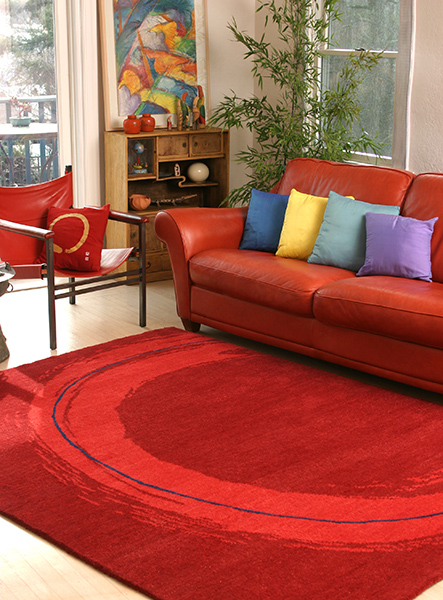 A bright red rug with an oval red shape sits under a red-orange couch in a living room