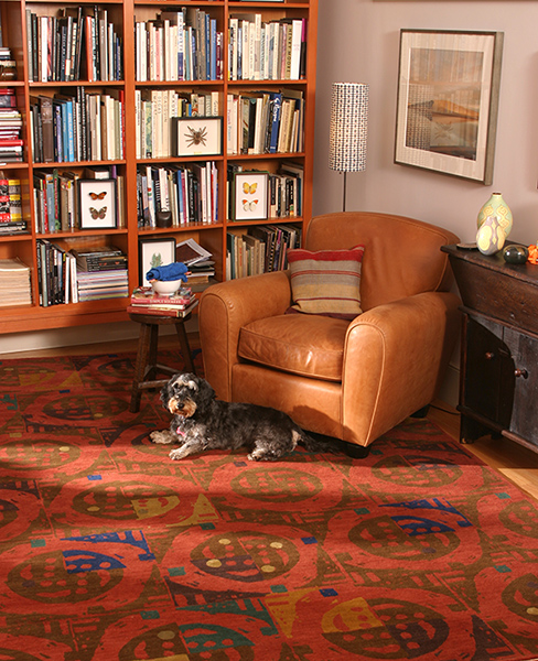 A reddish brown rug sits under a leather tan cushy chair in a library adorned with books and a cute dog