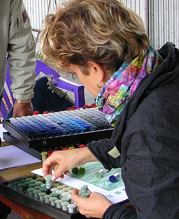 Artist Alicia D Keshishian leans over to select colors from a paletter for textile designs