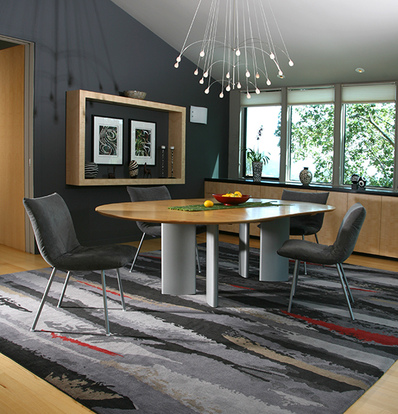A smokey colored rug on the floor of a dining room with wood and metal furniture